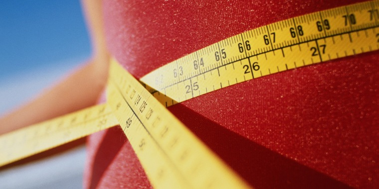 Teenage girl (13-15) measuring waist with tape measure, close-up