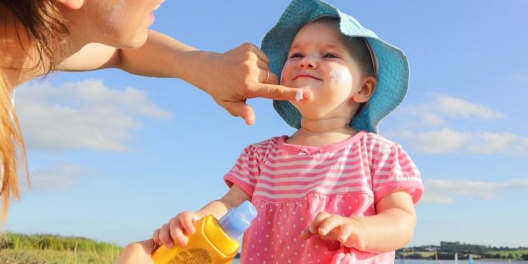 Mother putting sun cream on toddler girl outside