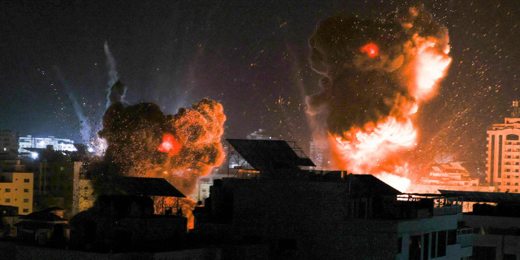 Image: Explosions light-up the night sky above buildings in Gaza City as Israeli forces shell the enclave