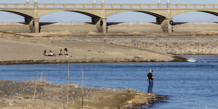Image:: A man fishes at the outtake of a water canal in Carson City on April 10,  2021 as Nevada enters a drought with water lines already showing low water levels.
