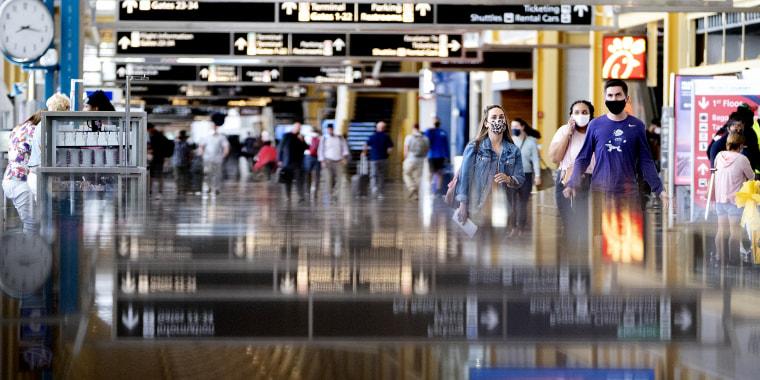 Travelers wearing protective masks walk through Ronald Reagan National Airport (DCA) in Arlington, Va., on May 25, 2021.