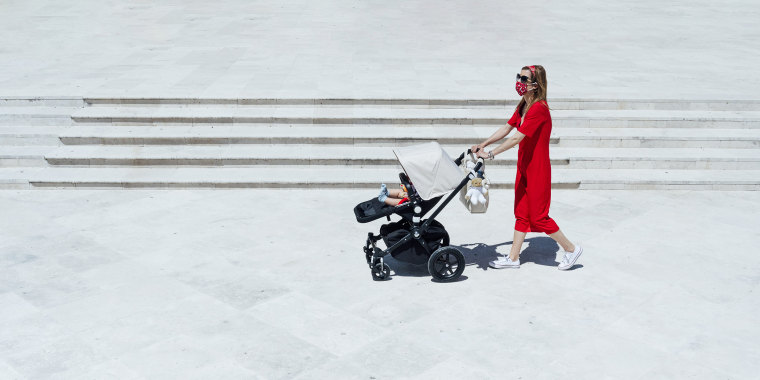 Mother wearing mask pushing son in baby carriage while walking on town square