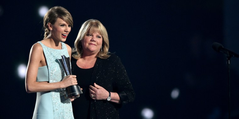 Taylor wift in a light blue gown hugs her mother in all black as she clutches a silver award