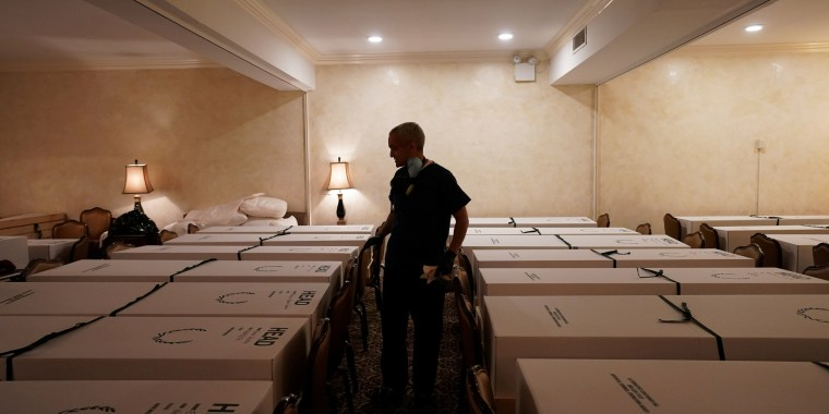 Image: A funeral director looks over caskets of bodies at the Gerard J. Neufeld funeral home during the coronavirus outbreak in New York City on April 26, 2020.