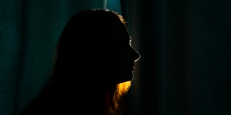 Image: Young woman silhouette in dark.