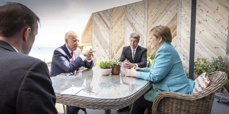 Germany's Chancellor Angela Merkel and President Joe Biden talk on the sidelines of the G7 summit in St. Ives, together with their foreign policy advisors Jan Hecker, second from right, and Jake Sullivan, left, on June 12, 2021, in Carbis Bay, Cornwall, E