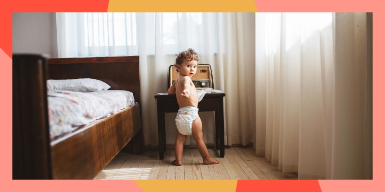 Portait of a 1 year old boy in a diaper in a bedroom