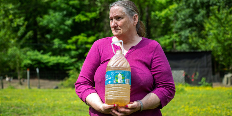 Hazel Cooper holds a jug of orange, contaminated water from one of her two wells. She and her husband have about $50 left every month after paying their bills, and use the money to buy bottled water.