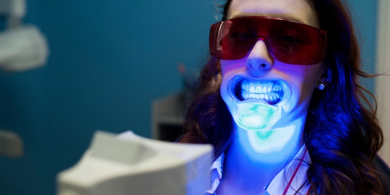 A woman wears protective eyewear during a teeth whitening session.