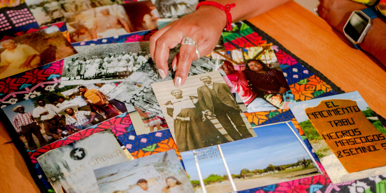 Historical photos displayed on a table including in the center a black and white photo of Corina Torralba Harrington's great grandmother, Effie Payne, whose Mexican name was Felipa Valdes, with her son, Ned Griner, whose Mexican name was Manuel Torralba, in Brackettville, Texas. Bottom right, is a photo of painted rock that marks the direction to Nacimiento de los Negros, Mexico where Juneteenth brings together descendants of Black Seminoles.