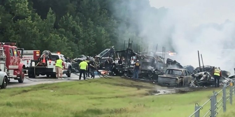 Image: Emergency personnel work at the accident site as smoke rises from the wreckage after about 18 vehicles slammed together on a rain-drenched Alabama highway during Tropical Storm Claudette, in Butler County, Alabama