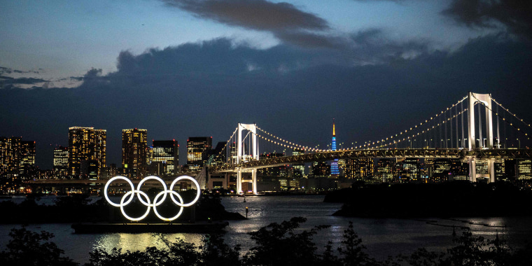 Image: The Olympic rings lit up at dusk on the Odaiba waterfront in Tokyo on May 31, 2021.