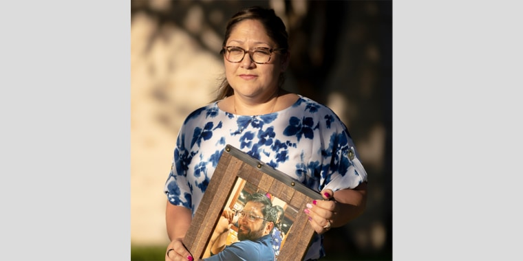 Image: Valerie Villegas holds a photograph of her late husband, Robert Villegas, taken on his 45th birthday, Nov. 10, 2020. Robert, a jiujitsu expert who worked as a truck driver, was strong and healthy before he contracted covid-19 in late December 2020.