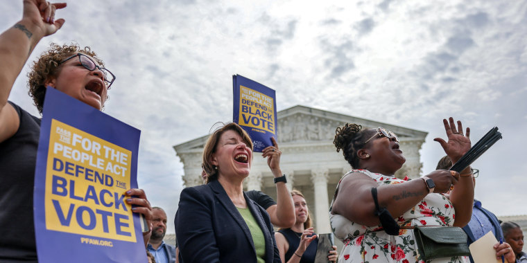Image: Senator Amy Klobuchar (D-MN) cheers during a rally outside the U.S. Supreme Court in Washington for voting rights