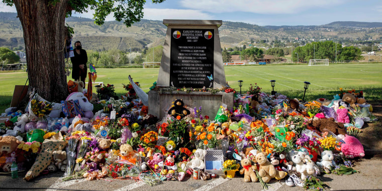 Image:  A makeshift memorial honoring the 215 children whose remains have been discovered buried near the facility surrounds a monument outside the former Kamloops Indian Residential School in Kamloops, British Columbia, Canada, on June 2, 2021.