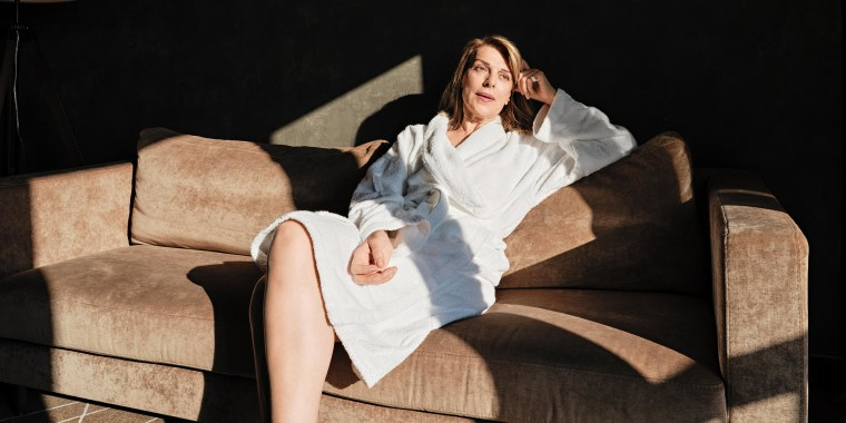 Thoughtful senior woman looking away while relaxing on sofa in hotel