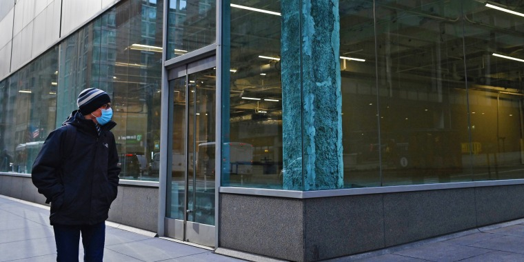 A man walks past an empty office building in the midtown area of Manhattan on Jan. 25, 2021.