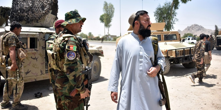 Image: Afghan security personnel stand guard along the road amid ongoing fight between Afghan security forces and Taliban fighters in Kandahar on July 9, 2021.
