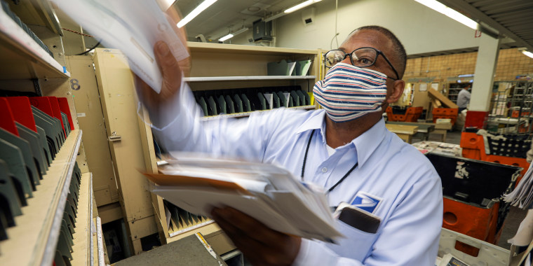 Image; A mailman sorts mail in his cubicle on May 15, 2020 in San Clemente, Calif.