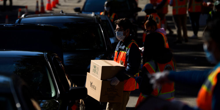 Image: Workers load boxes of groceries into vehicles at a mobile food distribution in Los Angeles on Feb. 5, 2021.