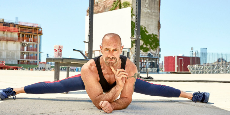 Meloni does the splits on concrete while looking inquisitively at the camera, one finger on his chin