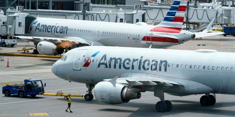 American Airlines passenger jets prepare for departure on July 21, 2021, near a terminal at Boston Logan International Airport.