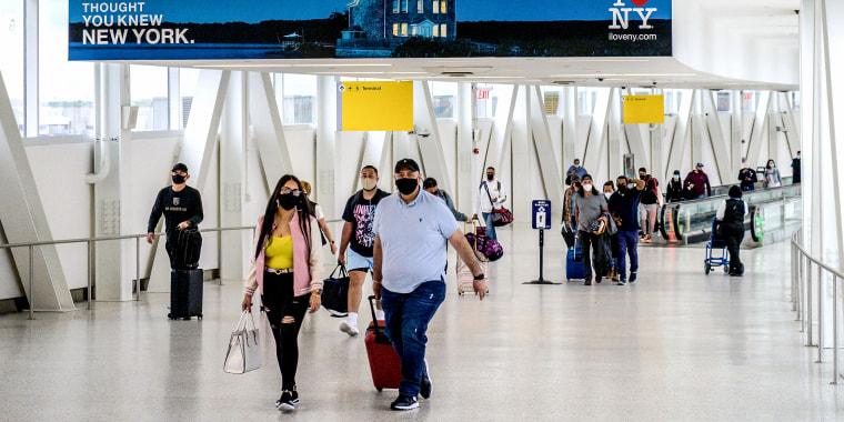 Travelers walk through John F. Kennedy Airport on May 28, 2021 in New York.