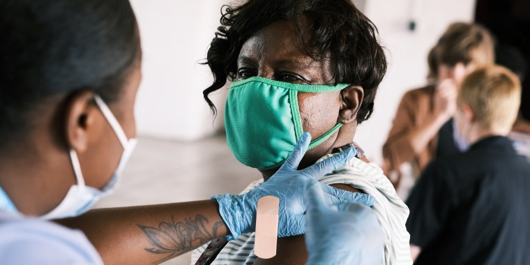 Image: A woman receives a Covid-19 vaccine on Aug. 4, 2021 in Ferguson, Mo.