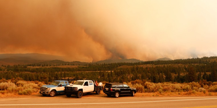 People watch as the Tamarack fire burns unchecked due to