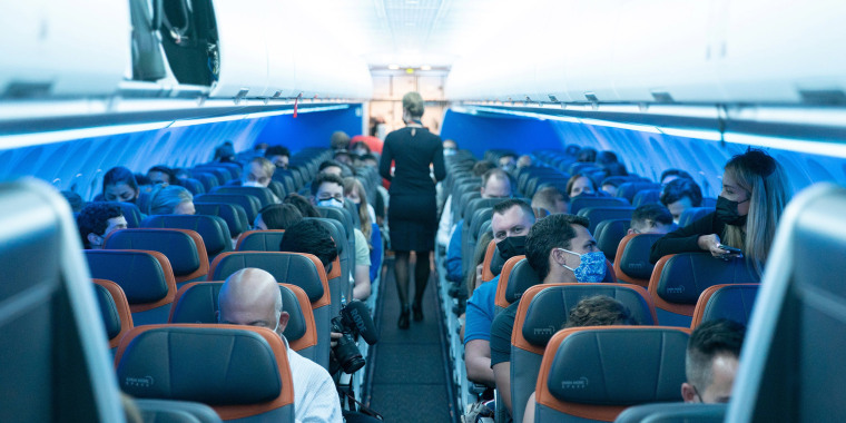 Image: Passengers wearing protective masks are seen aboard before a JetBlue flight to London at JFK International Airport, New York