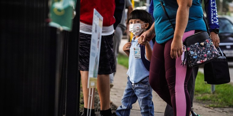 A student and his parents walk into an elementary school on the first day of school in Houston, Texas, on Aug. 23, 2021.