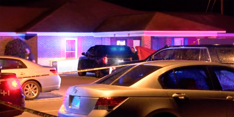 police lights illuminate a black parked SUV outside a low-rise brick building with yellow crime tape