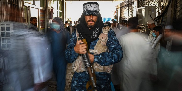 A Taliban fighter stands guard as people move past him at a market in Kabul on Sept. 5, 2021.