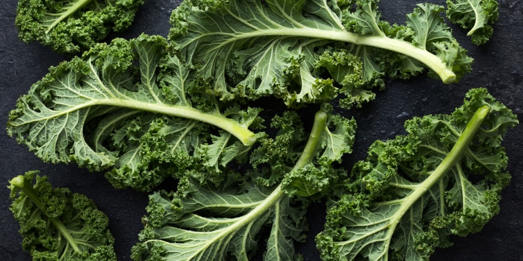 fresh green organic kale leaves on dark background