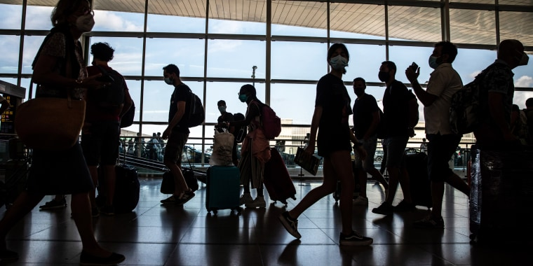 Travelers walk through the departures hall in El Prat airport in Barcelona on Aug. 2, 2021.