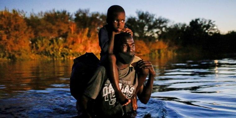 A migrant seeking refuge in the U.S. crosses the Rio Grande towards Del Rio, Texas, on Sept. 23, 2021.