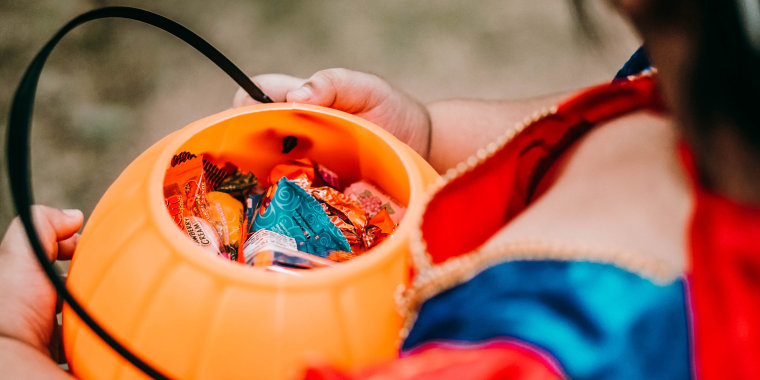 Little girl in costume holding trick or treat candy