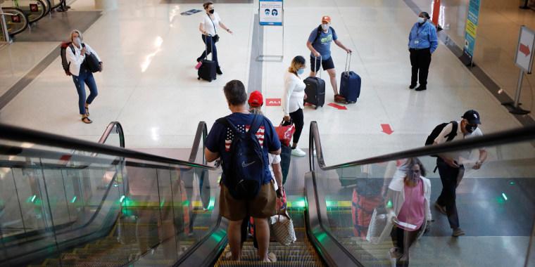 Travelers walk through Midway International Airport in Chicago, Illinois, U.S., on Monday, Oct. 11, 2021.