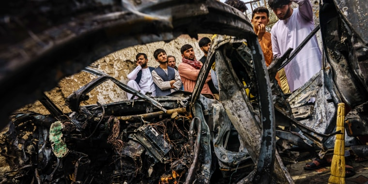 Image: Relatives and neighbors of the Ahmadi family gathered around the incinerated husk of a vehicle in Kabul, Afghanistan, on August 30, 2021.
