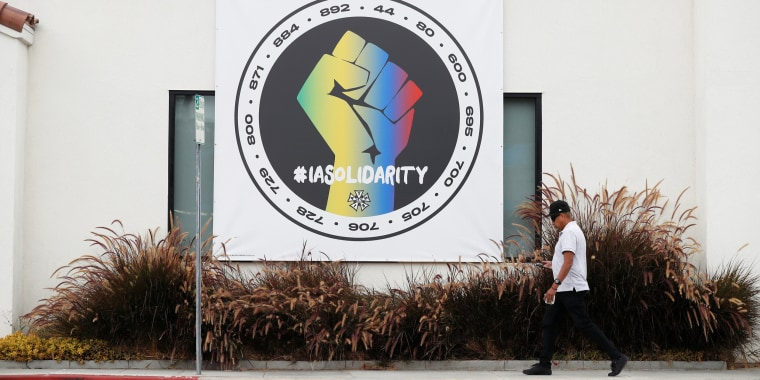 A person walks by a banner hung in support of the the International Alliance of Theatrical Stage Employees outside the Costume Designers Guild offices in Burbank, Calif., on Oct. 7, 2021.