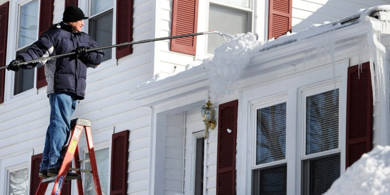 Image: A man rakes snow off the roof of his home in Windsor, Conn.