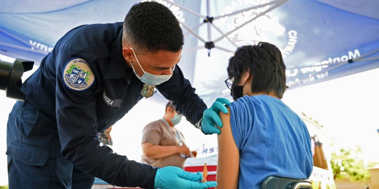 Brandon Rivera, a Los Angeles County emergency medical technician, gives a second does of Pfizer-BioNTech Covid-19 vaccine to Aaron Delgado, 16, at a pop up vaccine clinic in the Arleta neighborhood of Los Angeles, Calif., on Aug. 23, 2021.