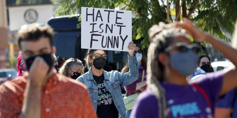 """A person in a jean jacket and face mask holds a sign that reads """"Hate isn't funny."""""""