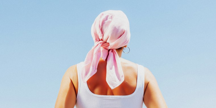 Rear view of a mature woman with cancer with a mask on the arm - stock photo.
