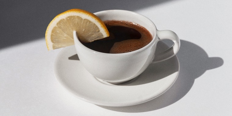 Coffee cup with espresso served with lemon on white background with shadows and sunlight