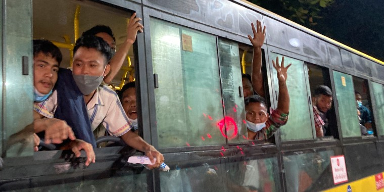 People wave from a bus after being released from Insein Prison in Yangon, Myanmar, on Monday. Thousands have been arrested since a military coup in February.