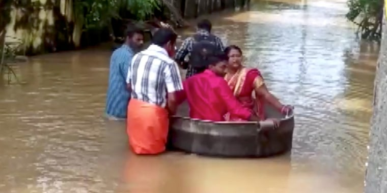 Image: Indian couple float to wedding venue in cooking vessel amid floods, in Alappuzha