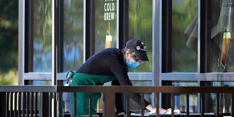A worker wears a face mask to help curb the spread of COVID-19 while sanitizing tables outside a Starbucks coffeehouse during a new coronavirus pandemic, Tuesday, April 27, 2021, in Orlando, Fla. (Phelan M. Ebenhack via AP)