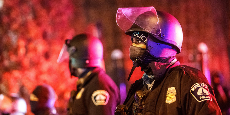 Image: Police keep guard as area residents gather at the site where a Minneapolis Police officer shot and killed a man in Minneapolis, on Dec. 30, 2020.