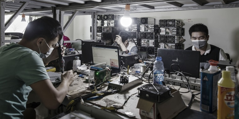 Technicians make repairs to bitcoin mining machines at a mining facility operated by Bitmain Technologies Ltd. in Ordos, Inner Mongolia, China, on Aug. 11, 2017.